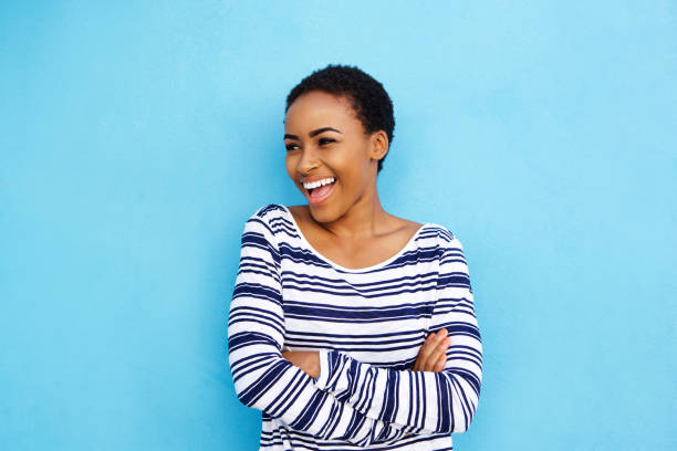 cool young black woman laughing against blue wall stock photo