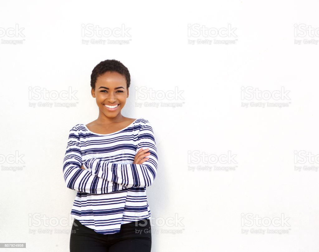 cool young black woman smiling against white wall stock photo