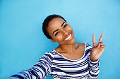 istock cool young black woman taking selfie with peace hand sign 857924534