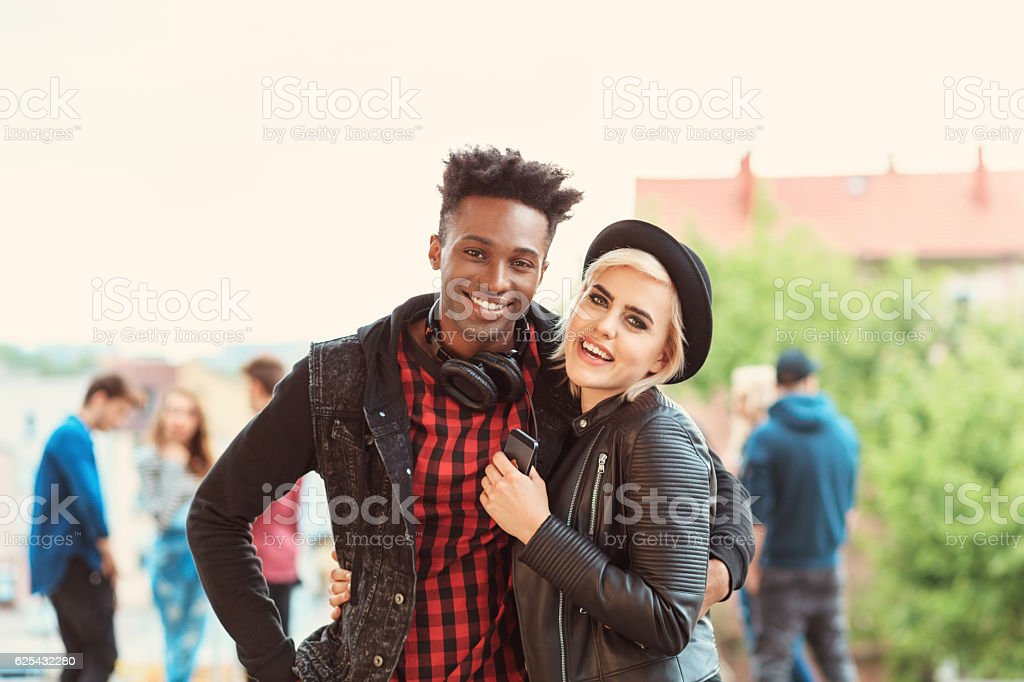 Cool young couple outdoor Outdoor portrait of funky young couple - afro amercian cool guy and beautiful blonde woman, laughing at the camera. Group of people in the background. 20-29 Years Stock Photo
