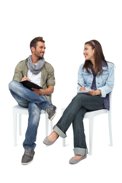 Cool young couple writing in notepads stock photo