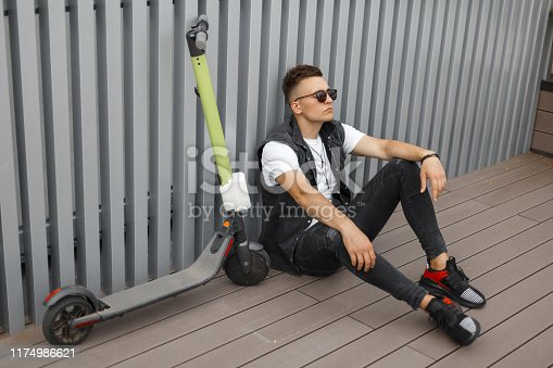 Cool young hipster man with hairstyle in black fashionable denim clothes in sunglasses with a scooter sit on a summer terrace in the city. Attractive guy resting on floor on the street
