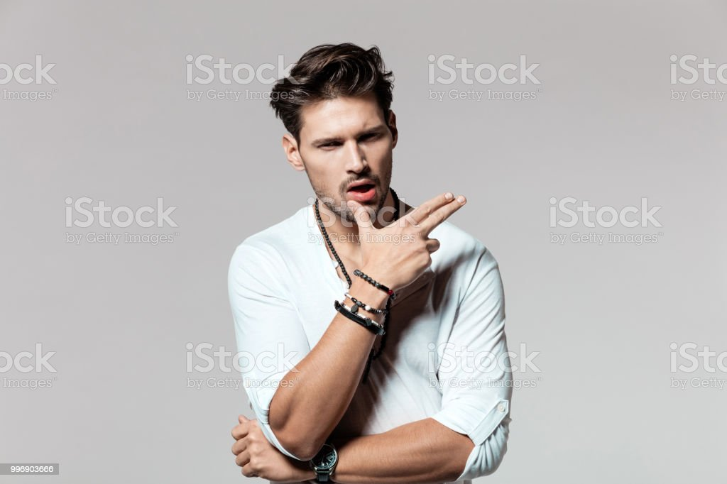 Cool young man in casuals Portrait of cool young man in casuals on grey background 25-29 Years Stock Photo