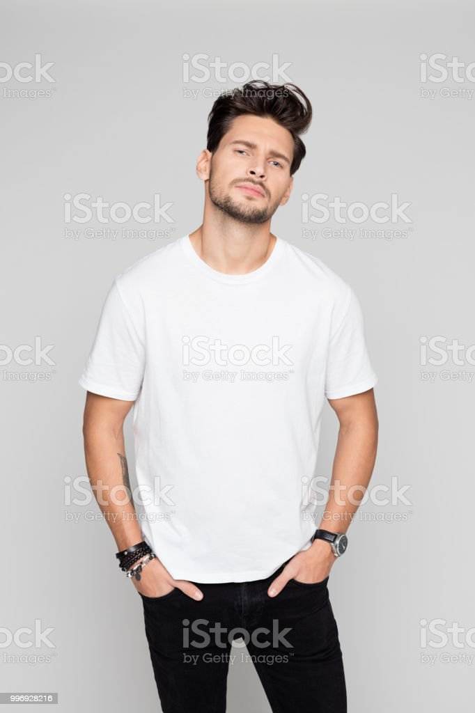 Cool young man standing on grey background Portrait of cool young man standing with his hands in pocket on grey background 25-29 Years Stock Photo