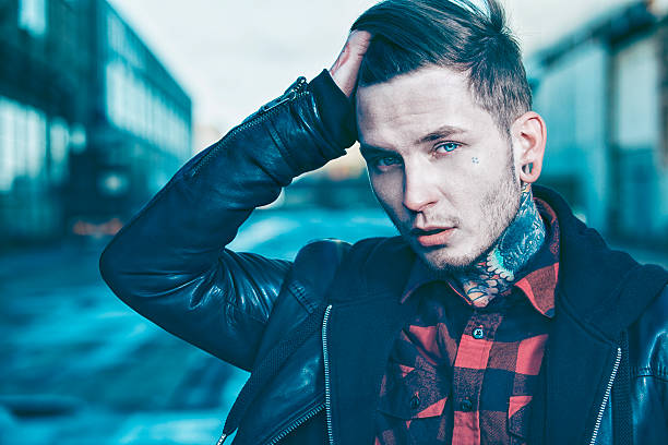 Cool young man with tattoos wears leather jacket stock photo