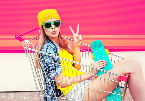 cool young smiling woman having fun sitting in trolley cart with skateboard over colorful pink background stock photo