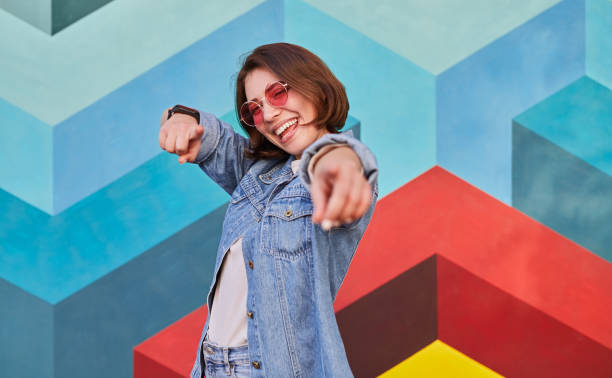 Cool young woman pointing at camera stock photo