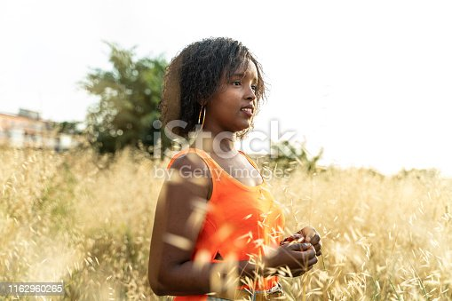 Cool young woman relaxing outdoors at a yellow field, wearing a vibrant orange top.