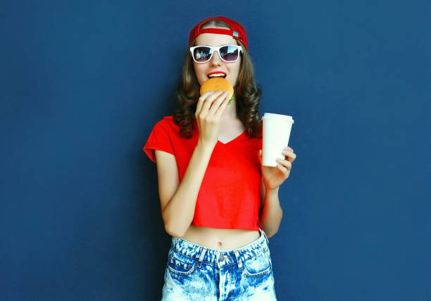 Cool young woman with burger and coffee cup wearing baseball cap, sunglasses over blue wall background stock photo