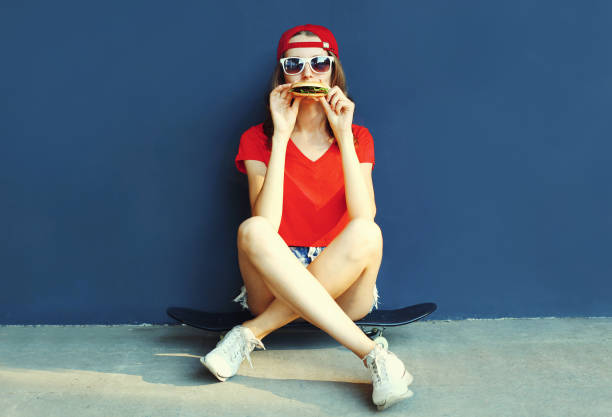 Cool young woman with burger sitting on skateboard wearing baseball cap, sunglasses over blue wall background stock photo
