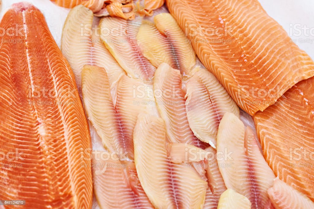 Cooled fish fillet of tilapia and salmon on store stock photo