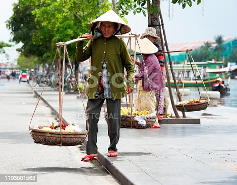 Coolie carrying wares, Hoi An, Central Vietnam. Hội An, a former port city known for the well-preserved Ancient Town, known for its canals and architecture, a mix of eras and styles from colourful French colonial buildings, wooden Chinese shophouses, temples, ornate Vietnamese tube houses and Japanese Covered Bridge with its pagoda -  central coast, Vietnam