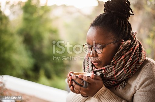 Shot of a young african woman blowing on a hot coffee to cool it off