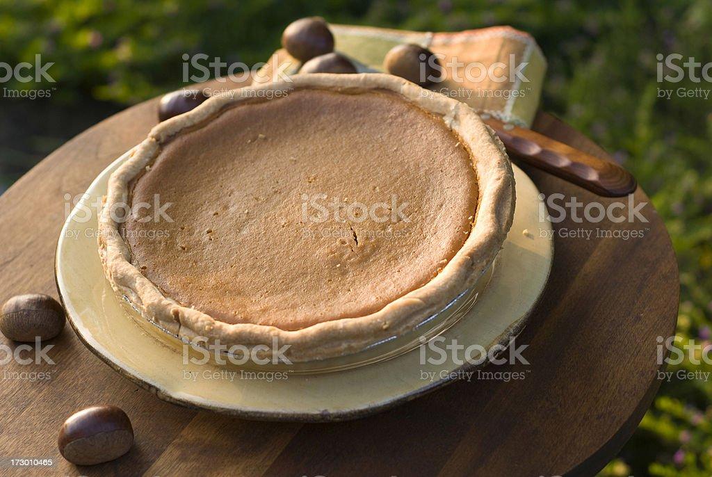 Cooling Autumn Pumpkin Pie: Homemade Thanksgiving Dessert & Chestnuts royalty-free stock photo