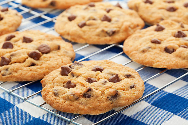 Cooling Cookies Warm, golden brown, chocolate chip cookies cooling on a rack.  Shallow depth of field.   chocolate chip cookie stock pictures, royalty-free photos & images