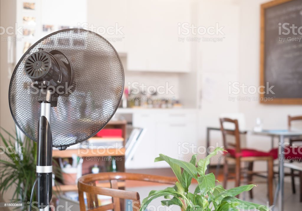 Cooling fan refreshing home room for summer stock photo
