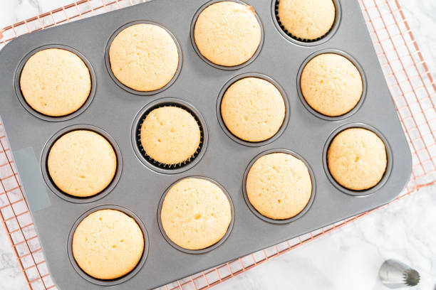 Cooling freshly baked vanilla cupcakes Cooling freshly baked vanilla cupcakes on a drying rack. muffin tin stock pictures, royalty-free photos & images