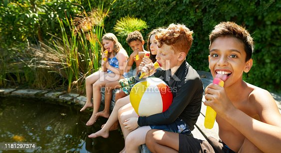 Shot of group of children sitting at outdoors pool on a summer day eating ice cream