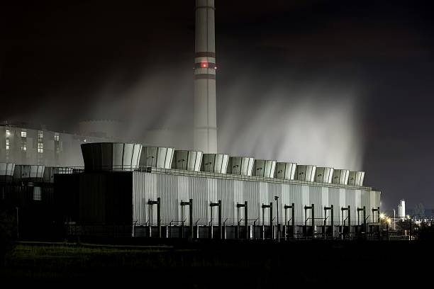 Cooling towers of a power plant at night stock photo