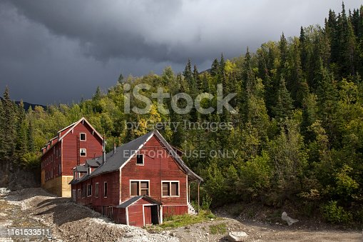Wrangell-St. Elias National Park, Kennecott, Alaska: Two red wooden cooper mill buildings by a conifer forest in a stormy day