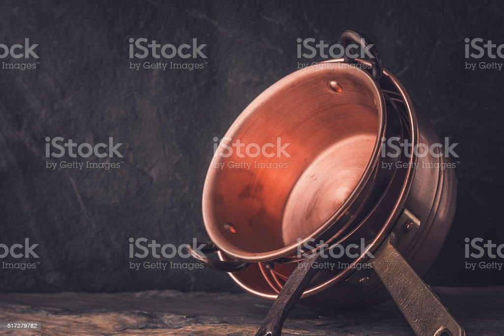 Cooper pots and pans on the stone table horizontal stock photo