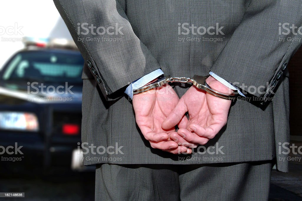 Cooperate Businessman in Hand Cuffs In Front of Police Car royalty-free stock photo