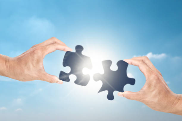 Cooperate for successful work with businessman holding jigsaw puzzle, concept of partnership stock photo