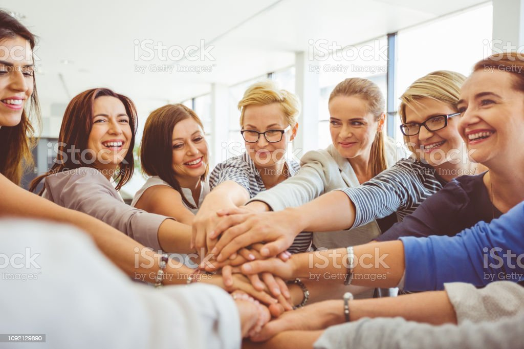 Cooperation and teamwork business concept Happy group of women putting their hands together and smiling. Female with stack of hands showing cooperation and teamwork. A Helping Hand Stock Photo