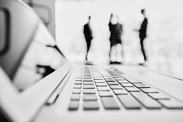 Cooperation behind laptop stock photo