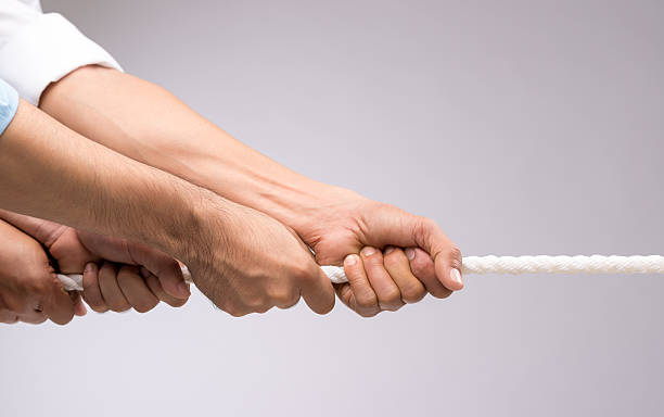 Cooperation concept Hands of people pulling the rope: cooperation concept pulling stock pictures, royalty-free photos & images