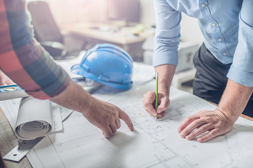 Hands of an architect and an engineer pointing at the architectural plan. they have a coordination meeting to make sure everything works