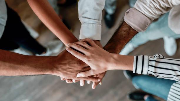 협력. 사무실에 서있는 동안 함께 손을 잡고 사람들의 최고 보기 - 책임 뉴스 사진 이미지