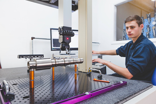 Coordinate measuring machine (CMM) . The device is being programmed by a young male to measure the physical geometrical characteristics of an object. The operator is concentrating on the procedure. A display screen is seen in the background.