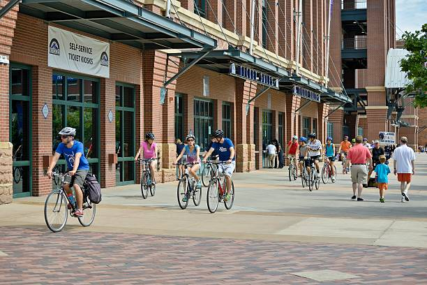 Coors Field Denver, Colorado, USA - August 11, 2013: Streetside view of people on bikes and pedestrians at Coors Field, home to the MLB Colorado Rockies and named after the brewing company from Golden, Colorado. major league baseball stock pictures, royalty-free photos & images