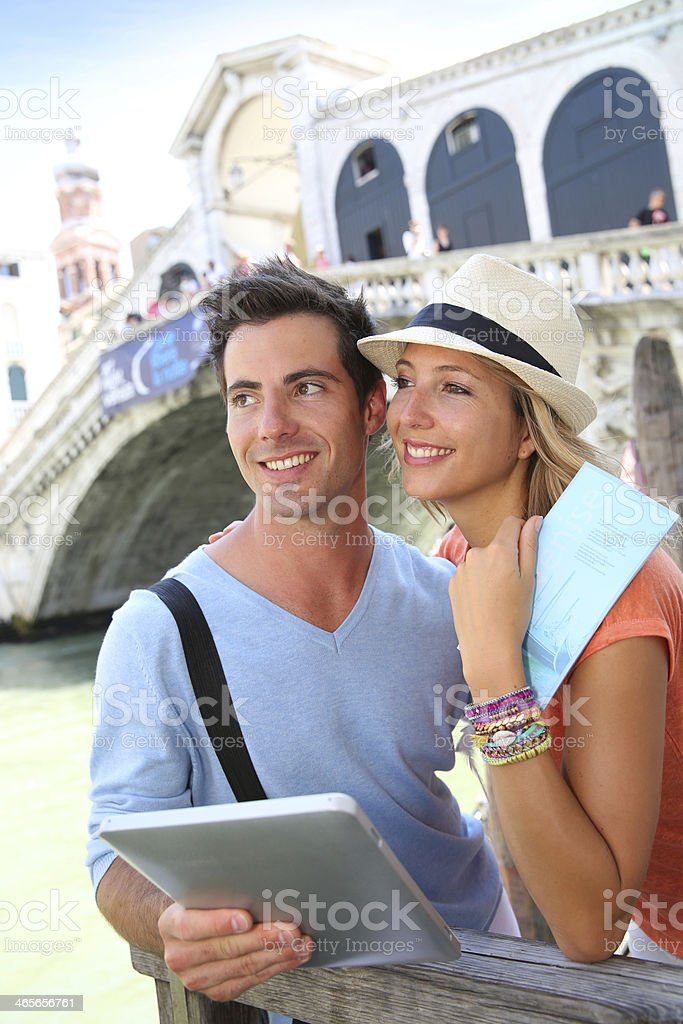 Coouple in love visiting Rialto Bridge with help of tablet royalty-free stock photo