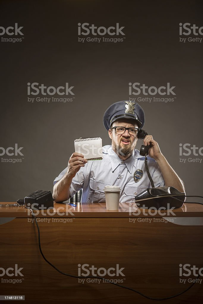 Cop on the Phone with Frustrated Expression stock photo