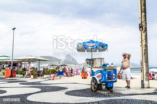 Rio de Janeiro, Brazil - October 27, 2013: Ice cream street vendor at Copacabana beach, one of the most traditional beach in Rio de Janeiro. The sidewalk has plenty of kiosks and street vendors to serve locals and tourists. On the background is the Sugarloaf mountain.