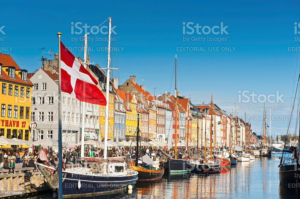 Copenhagen Danish flag flying over Nyhavn colourful harbour stock photo