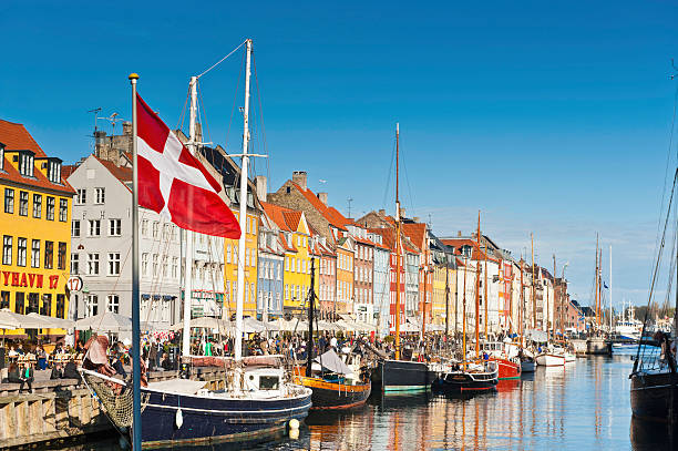 copenhagen danish flag flying over nyhavn colourful harbour - denmark stock photos and pictures