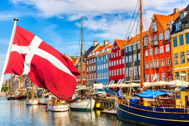 köpenhamns ikoniska vy. berömda gamla nyhavn hamn i centrala köpenhamn, danmark under sommaren solig dag med danmark flagga på förgrunden. - öresundsregionen bildbanksfoton och bilder