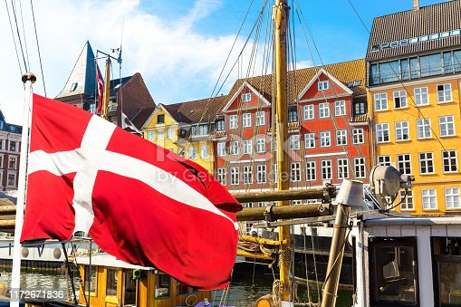 istock Copenhagen iconic view. Famous old Nyhavn port in the center of Copenhagen, Denmark during summer sunny day with Denmark flag on the foreground. 1172671836