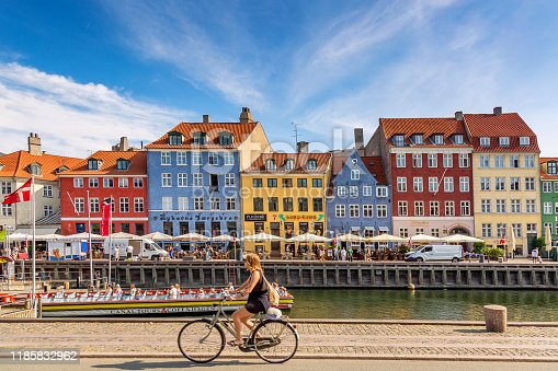istock Copenhagen iconic view. Famous old Nyhavn port with colorful medieval houses, tourist ship and woman on a bicycle in the center of Copenhagen. Selective focus 1185832962