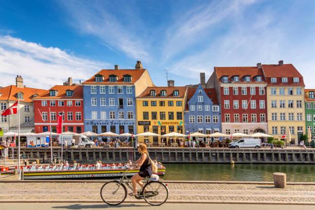 köpenhamns ikoniska vy. berömda gamla nyhavn hamn med färgglada medeltida hus, turist skepp och kvinna på en cykel i centrala köpenhamn. selektivt fokus - öresundsregionen bildbanksfoton och bilder
