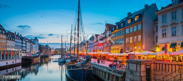 The iconic colourful restaurants and busy al fresco cafe bars of Nyhavn warmly illuminated beside the sailing ships moored beneath sunset skies in the heart of Copenhagen, Denmark's vibrant capital city.