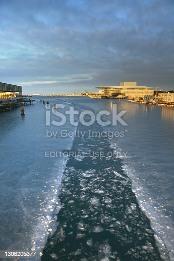 Sunlit Danish Opera House with frozen water in the canal of the inner harbour on a sunny winter day in Copenhagen, Denmark