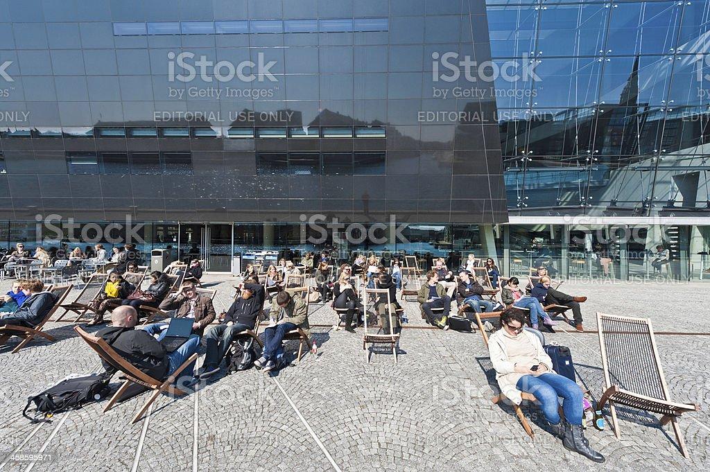 Copenhagen people relaxing in chairs outside Black Diamond library Denmark stock photo
