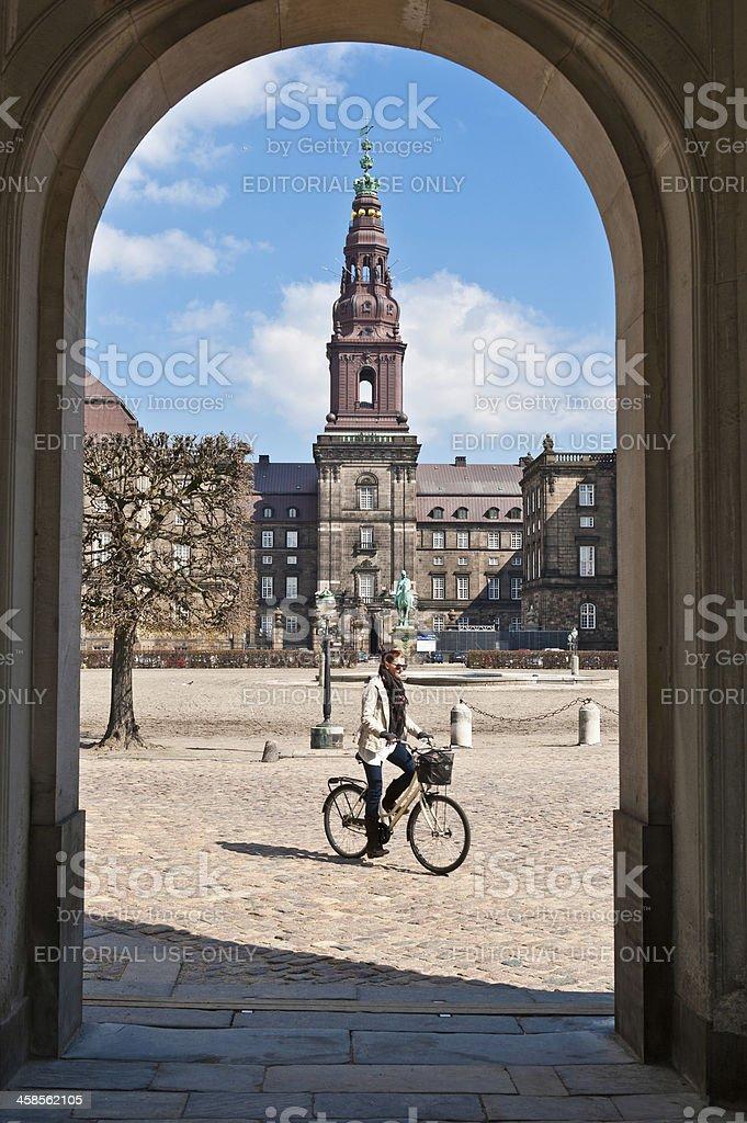 Copenhagen woman cycling through Christiansborg Palace stock photo