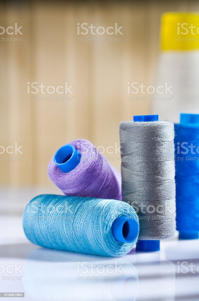 copmosition of sewing spools on white table stock photo