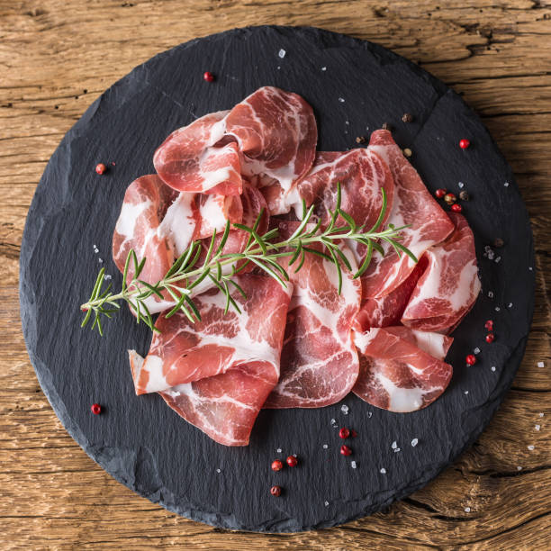 Coppa di Parma ham on slate board with rosemary salt and pepper stock photo