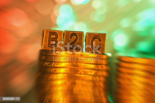 B2C copper alphabet on coin stack in radial blur illuminated with light